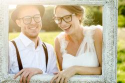 lachendes Brautpaar hält einen Vintage Bilderrahmen