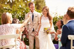 frisch getrautes Ehepaar inmitten der Hochzeitsgesellschaft
